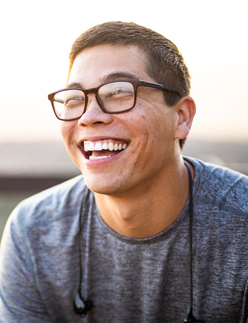 A young man with glasses smiling