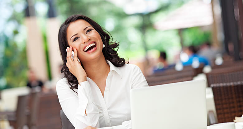 A woman talking on her phone while smiling