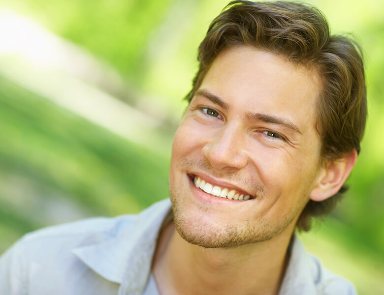 A brunette man smiling outdoors