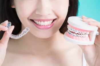 Woman holding up Invisalign retainer and traditional braces