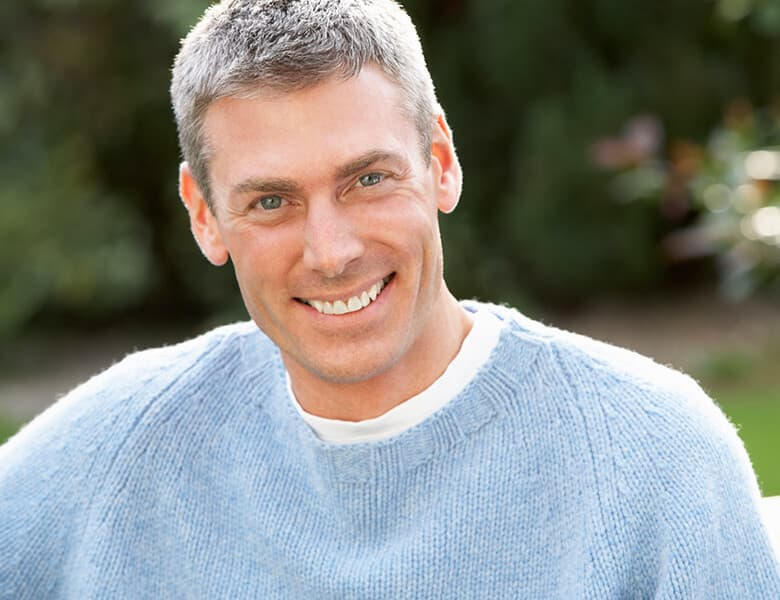 Man with gray hair smiling outdoors