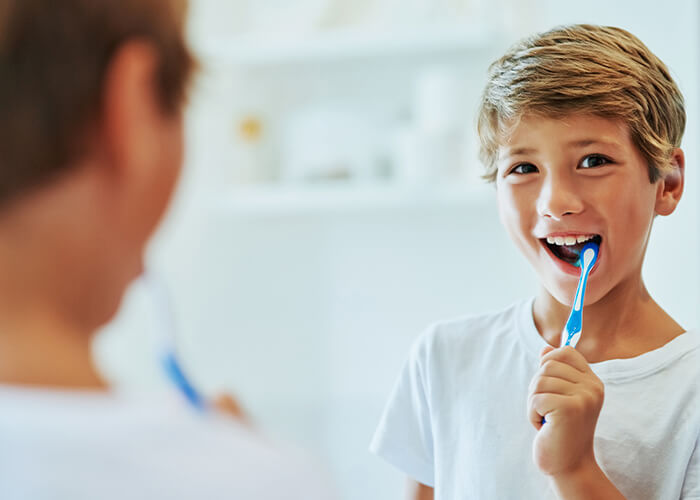 A young boy brushing his teeth in front of the mirror