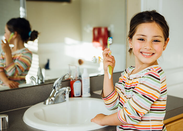 A young girl holding her toothbrush up