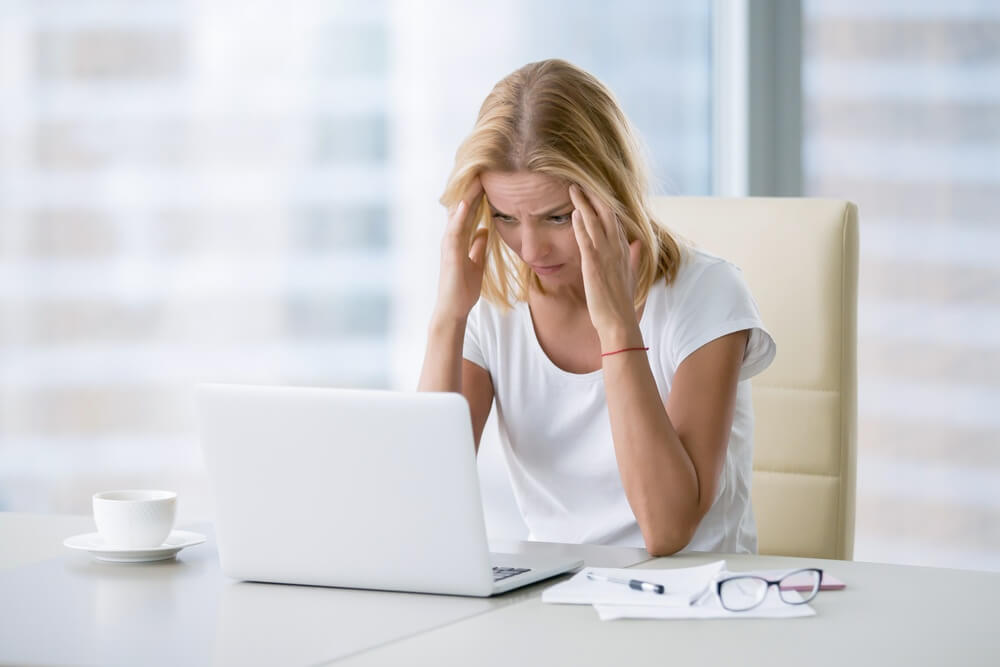 Woman sitting at her computer stressed out