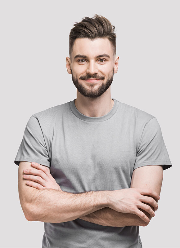 A young man with gray t-shirt on a gray background smiling