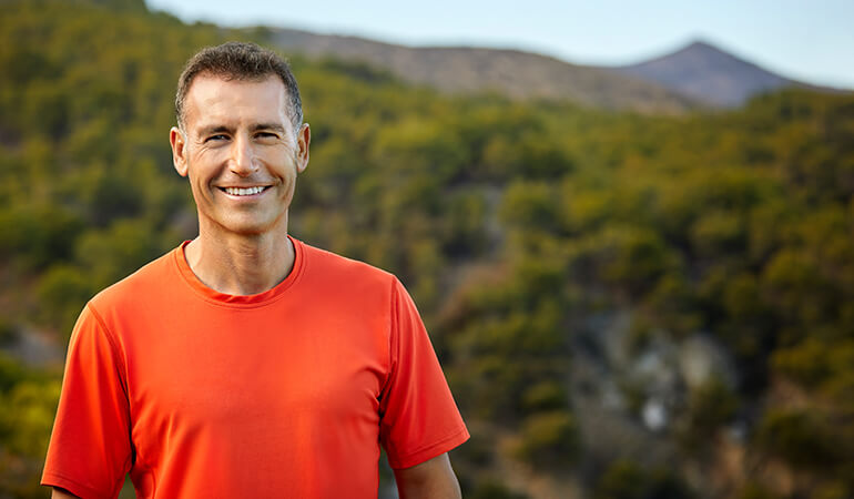 A man wearing an orange t-shirt smiling outdoors
