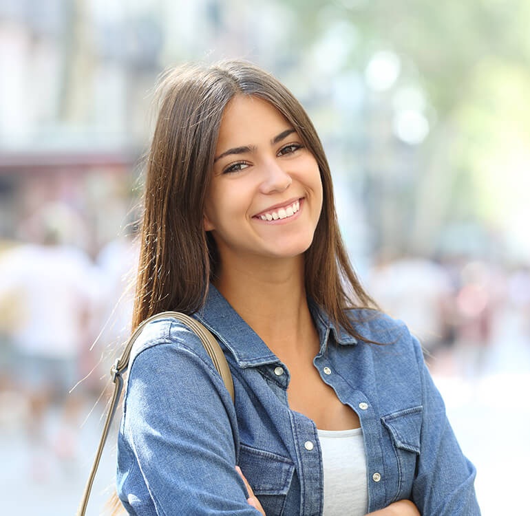 A young woman with brown hair smiling outdoors